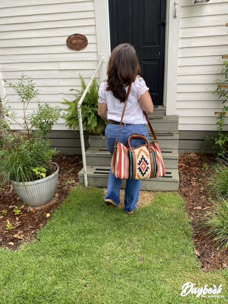 lady walking with bag into a cottage