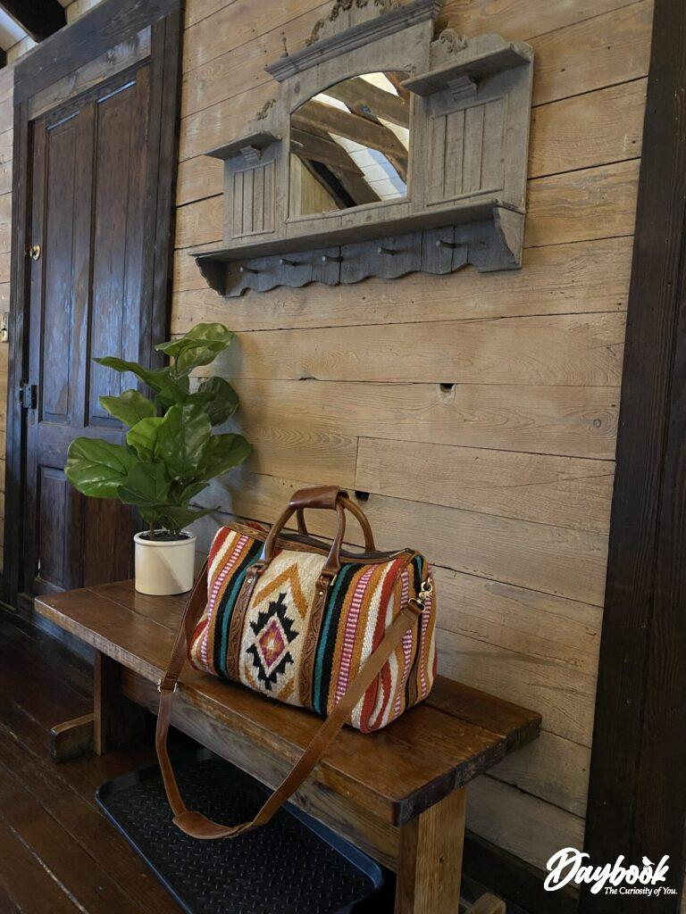 Ariat bag on a wooden bench inside a cottage