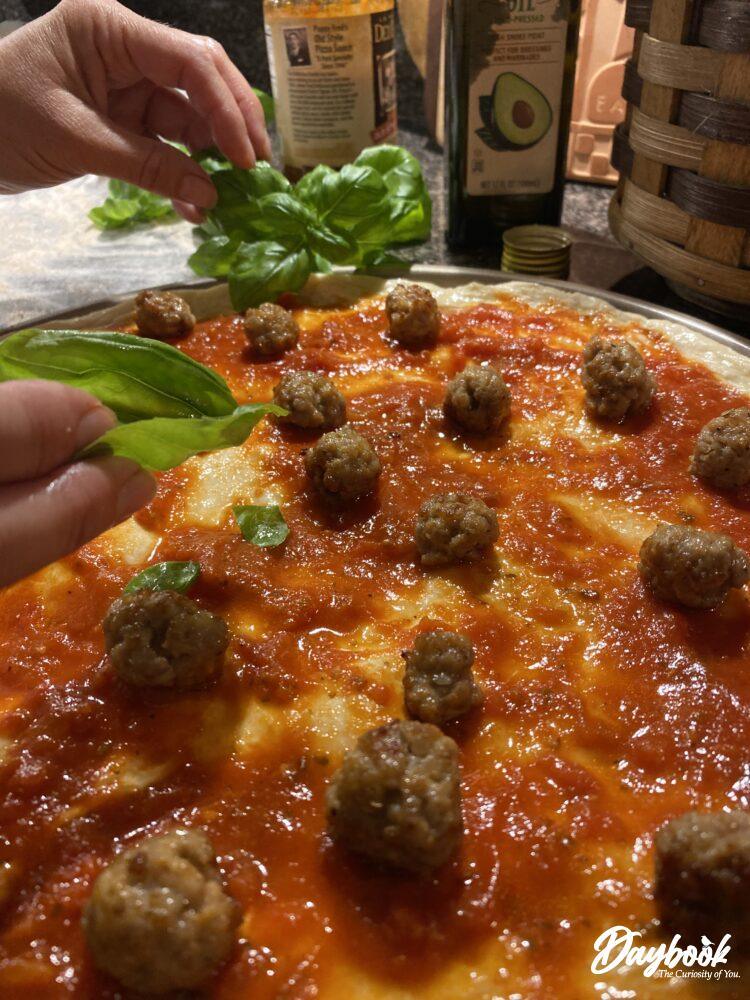 fresh basil being placed on a pizza