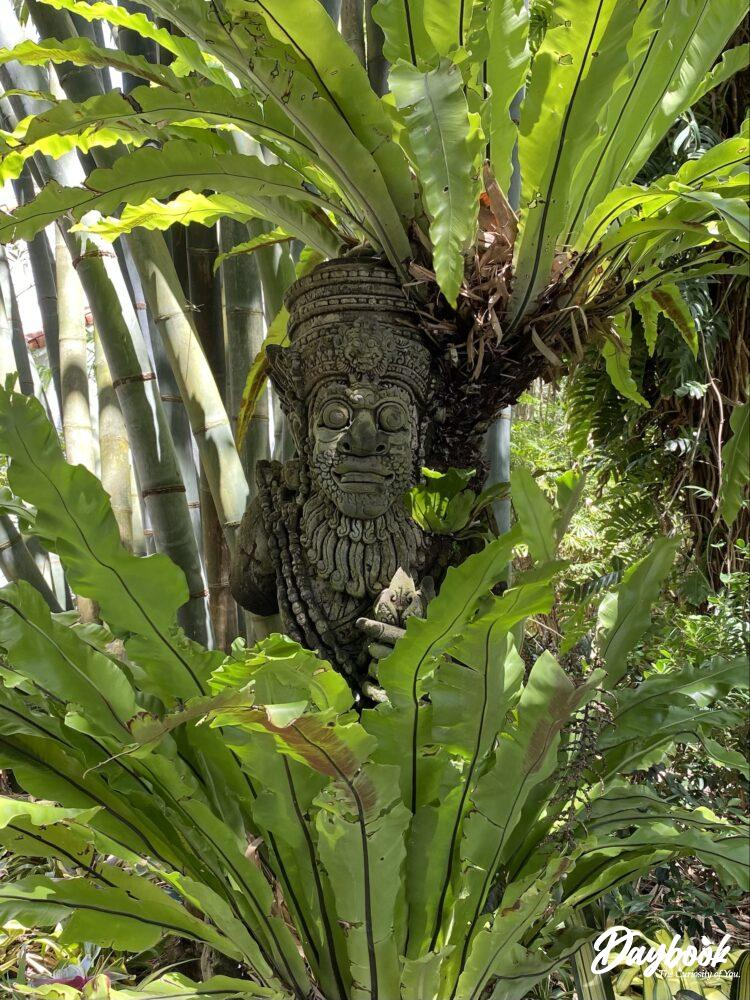 wood carving amongst palm trees and bamboo