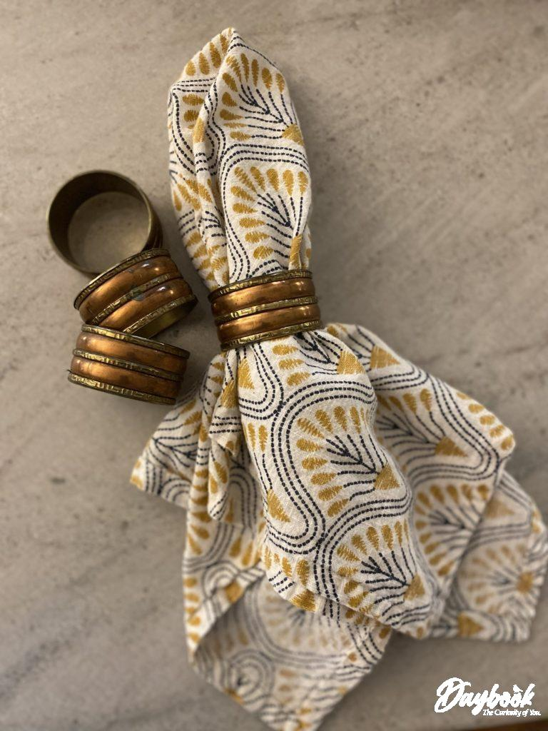 Four brass and copper napkin rings with one cloth napkin