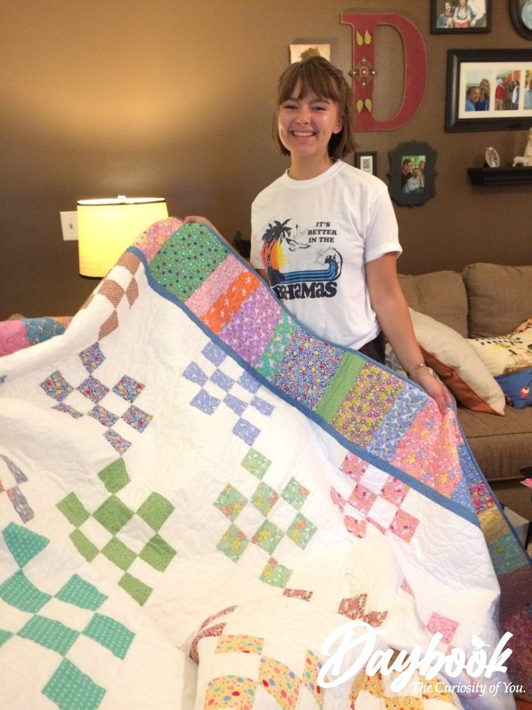 handmade quilt held up by young girl