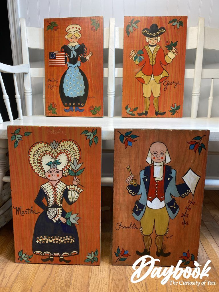 Four Americana folk art pieces displayed on a white bench