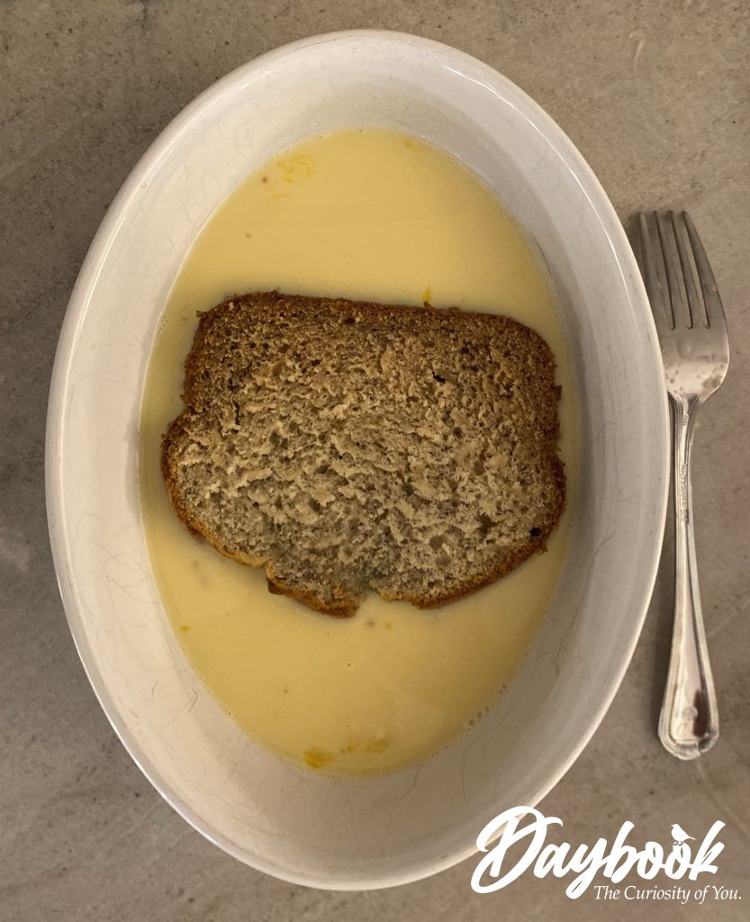 one slice of banana bread soaking in an egg and milk mixture